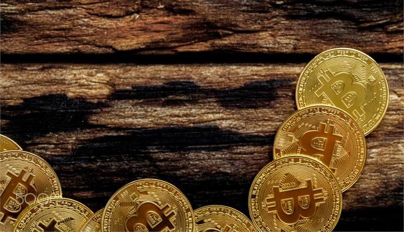 سکه طلایی بیتکوین روی میز چوبی